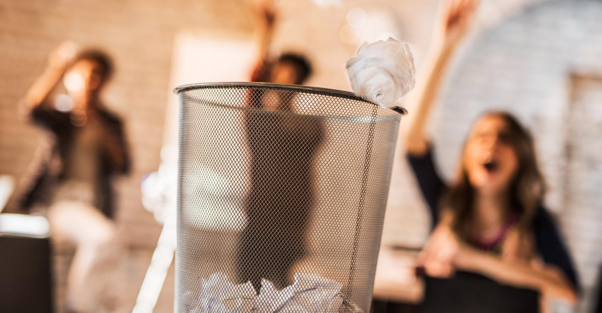 Frauen im Büro werfen zerknittertes Papier in Mülleimer
