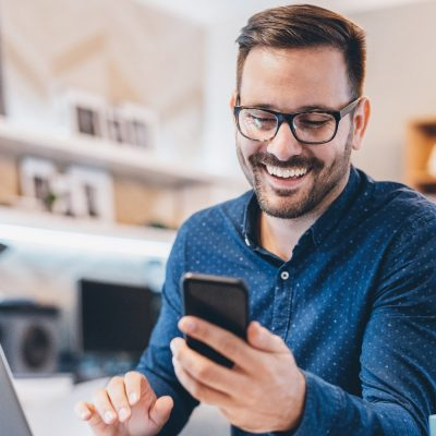 Geschäftsmann mit Smartphone im Home-Office