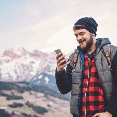 Mann sieht bei Wanderung auf Smartphone