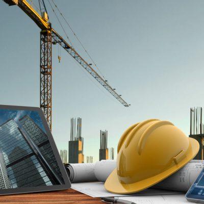 Ein Kran auf einer Baustelle mit Tablet im Vordergrund