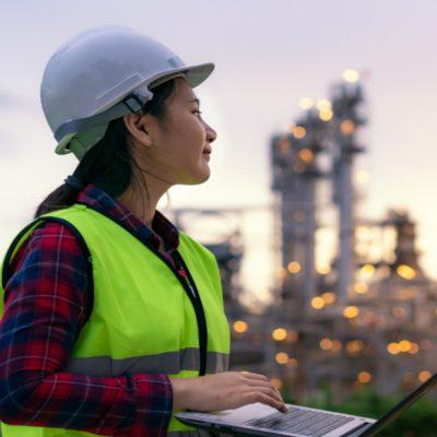 Eine Frau steht mit einem Notebook in der Hand vor einer Industrieanlage.