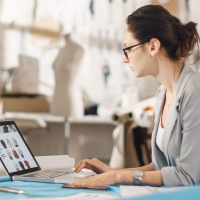 Eine junge Designerin sitzt in einem Modeatelier an ihrem Schreibtisch und blickt auf Skizzen auf einem Laptop.