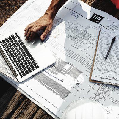 Architekt beugt sich über Bauzeichnungen und Laptop.