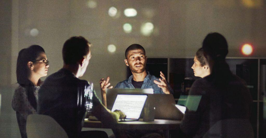Eine Gruppe von Mitarbeitern diskutiert bei einem Meeting.
