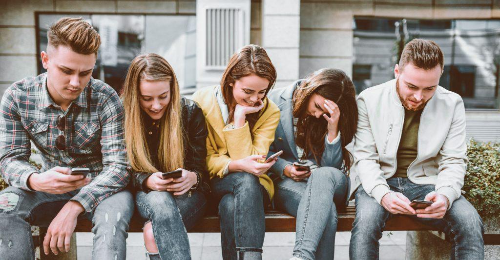 Fünf junge Leute sitzen auf einer Bank und blicken auf ihre Smartphones.