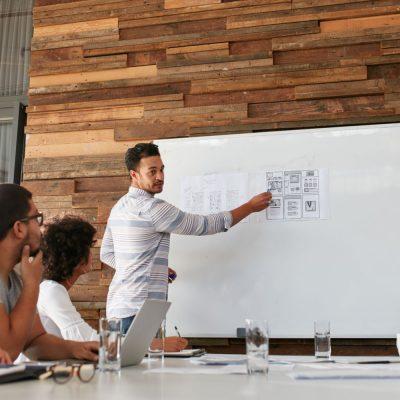 Entwickler zeigt ein Vorgehen in einer Agentur auf einem Whiteboard