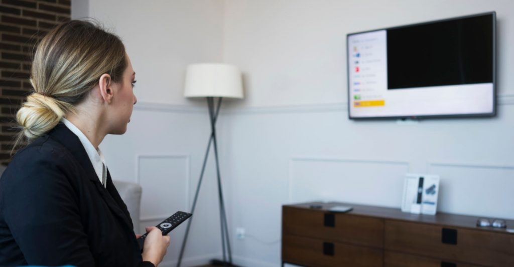 Junge Geschäftsfrau betrachtet geschäftliche Unterlagen auf einem Hotelfernseher.