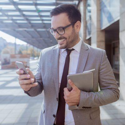 Geschäftsmann schaut unterwegs auf sein Smartphone
