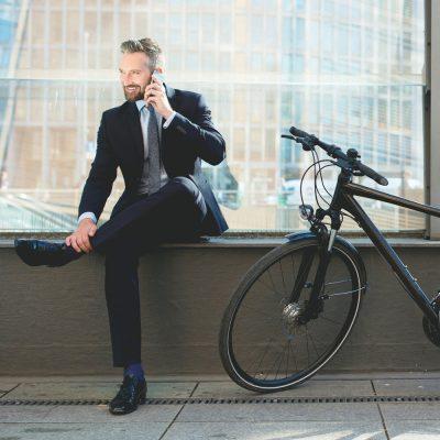 Geschäftsmann telefoniert neben einem Fahrrad
