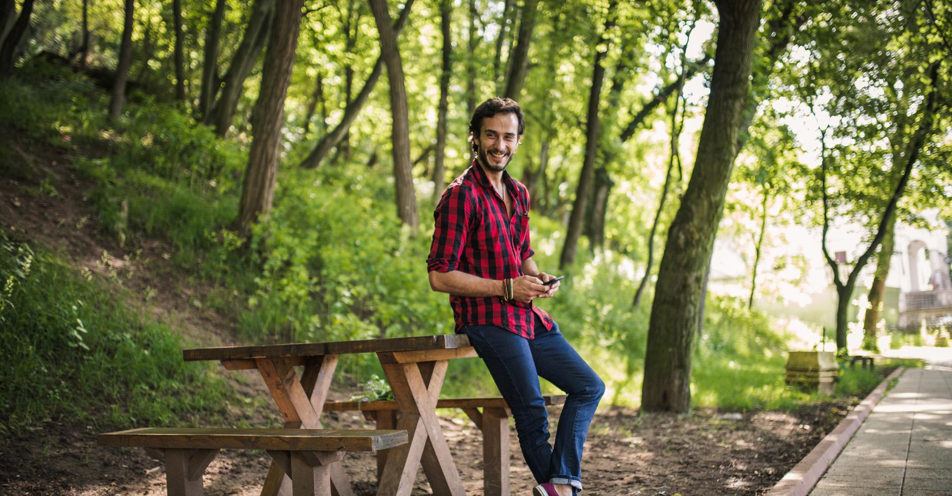 Junger Geschäftsmann mit Smartphone im Wald