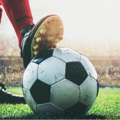 Fussballer-Füße und ein Fussball in einem Stadion
