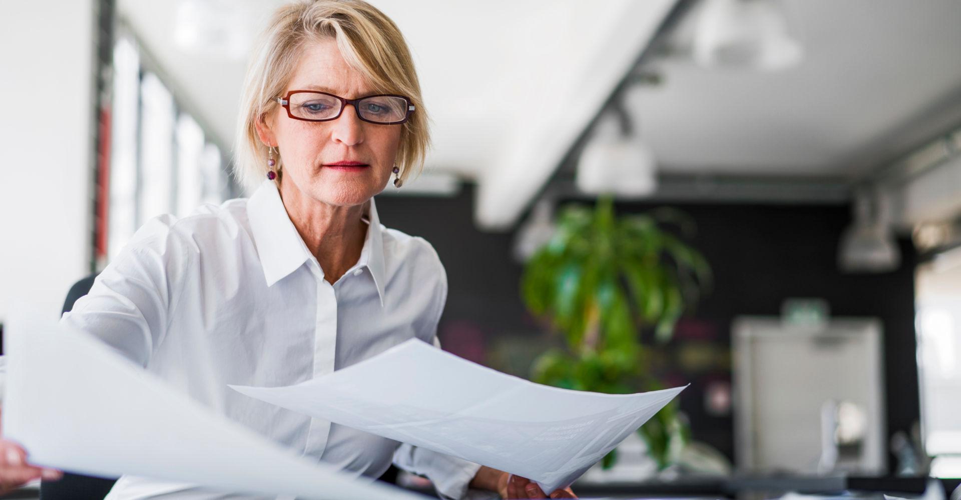 Unternehmerin sitzt über Unterlagen