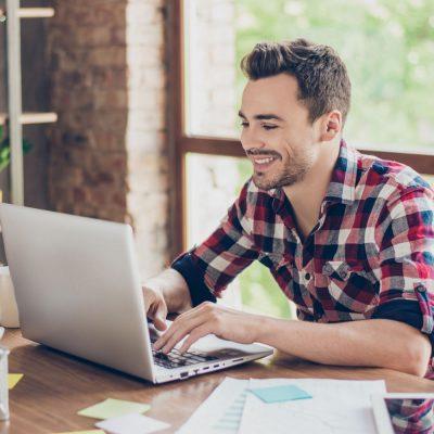 Unternehmer sitzt vor dem Laptop im Büro