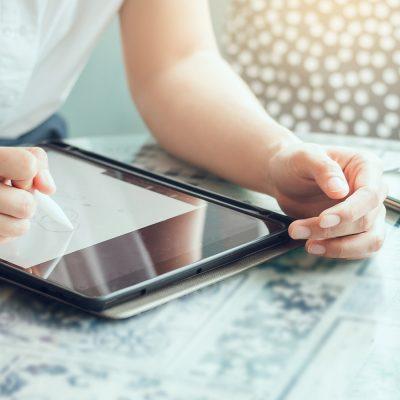 Frau schreibt mit Smart Pen auf Tablet