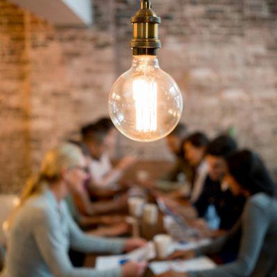 Eine Glühbirne hängt über einem Tisch, an dem junge Mitarbeiter diskutieren