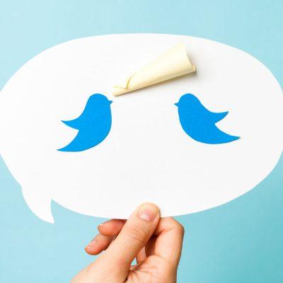 Eine Hand hält eine Sprechblase mit dem Twitter-Logo