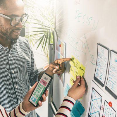Frau mit Smartphone und Mann vor Flipboard besprechen User Interface