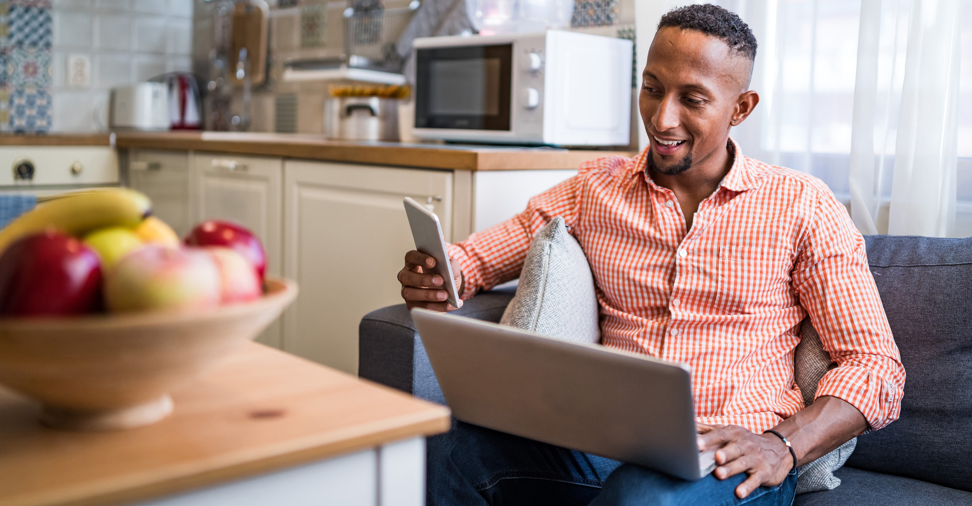 Mann sitzt zuhause in der Küche beim Onlineshopping