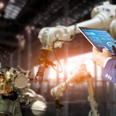 Mann mit Tablet steuert eine Gruppe von Robotern, die ein Bauteil fertigen
