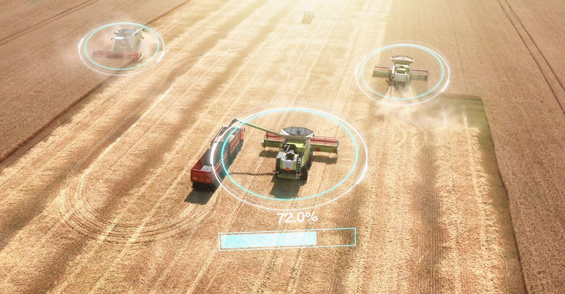 Symbolbild mit Mähdreschern, die ein Feld automatisiert abernten