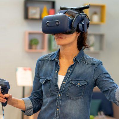 Eine Frau spielt mit VR-Brille und VR-Controller.