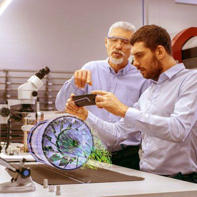 Zwei Ingenieure sehen ein Bauteil als Hologramm vor sich auf einem Tisch.