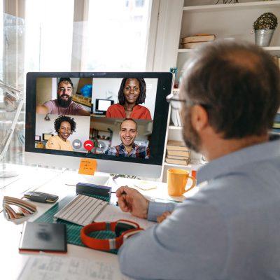 Zwei Mitarbeiter nehmen an einer Videokonferenz teil