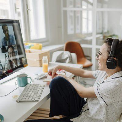 Eine junge Frau sitzt im Homeoffice und nimmt an einem Videomeeting teil