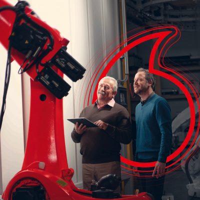 Zwei Männer stehen mit Tablet vor einem Roboter