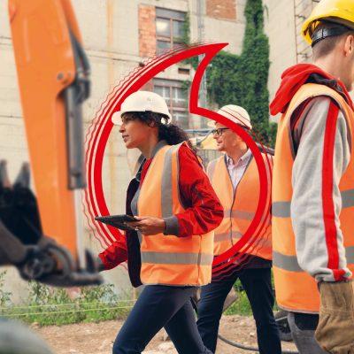Eine Frau und zwei Männer in Warnwesten stehen auf einer Baustelle.