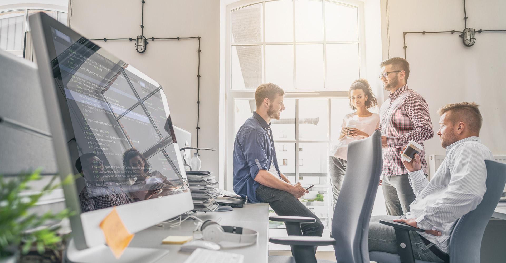 Mitarbeiter diskutieren im Büro einen Projektfortschritt