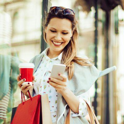 Junge Frau beim Shoppen mit Smartphone
