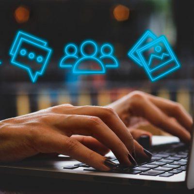 Laptop mit Social-Media-Symbolen und Händen