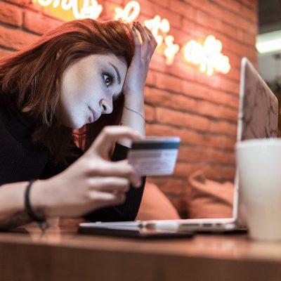 Junge Frau im Cafe mit Laptop und Kreditkarte