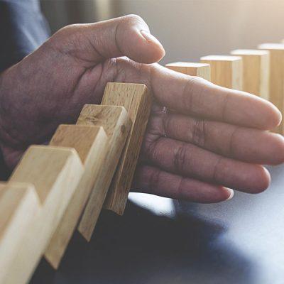 Krisenmanagement: Eine Hand stoppt eine umfallende Reihe Dominosteine.