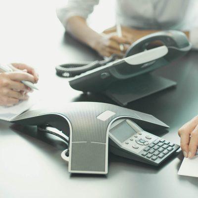 Eine Frau und drei Männer sitzen in einem Konferenzraum und hören einer Telefonkonferenz zu.