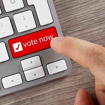 """Ein Finger bewegt sich auf eine mit """"vote now"""" beschriftete Taste auf einem Notebook zu."""