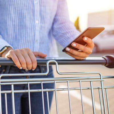 Frau mit Einkaufswagen und Smartphone