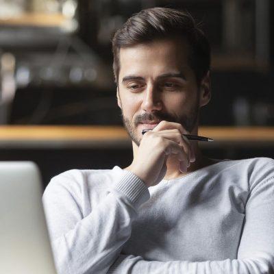 """Ein junger Mann sitzt entspannt vor seinem Notebook und folgt einem Webinar."""""""