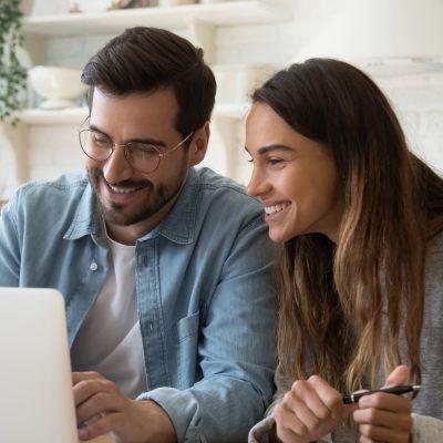 Junges Paar informiert sich am Laptop über Fördermittel