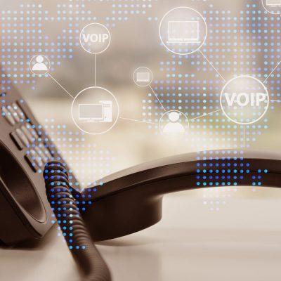 Ein Telefonhörer liegt neben einem SIP-Telefon auf einem Schreibtisch
