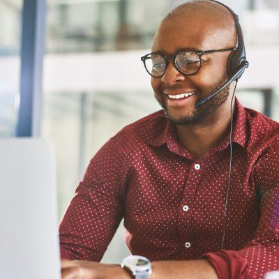 Ein Mann sitzt im Büro und telefoniert über ein Headset via Internet