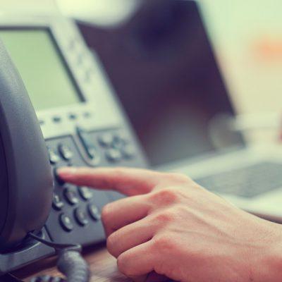 Ein Büroangestellter wählt auf einem Systemtelefon eine Nummer