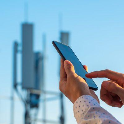 Smartphone-Nutzer vor einem Sendemast