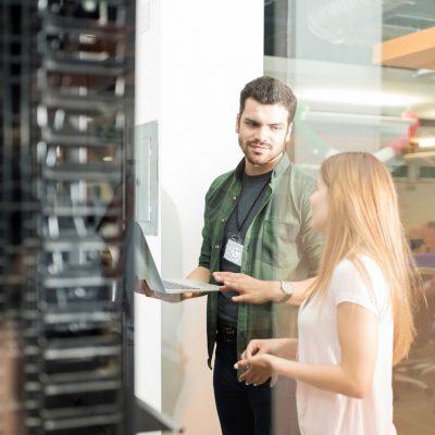 Zwei Mitarbeiter an einem Serverschrank in der Nähe ihres Büros