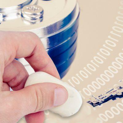 Eine Person streicht mit einem Radiergummi über eine Festplatte, Symbolfoto
