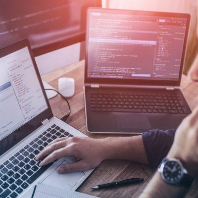 Entwickler bei der Arbeit an zwei Laptops