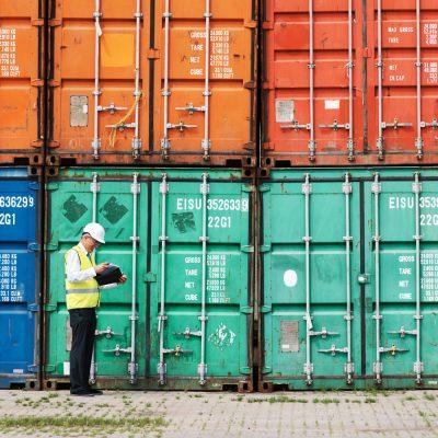 Mitarbeiter prüft den Zustand mehrerer ISO-Container