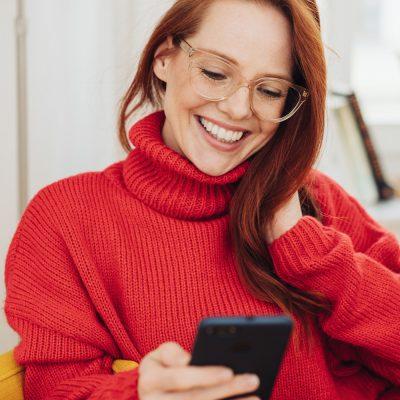 Junge Frau nutzt Rich Business Messaging auf ihrem Smartphone