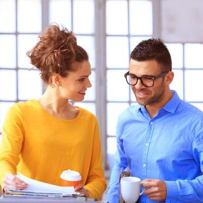Eine Frau und ein Mann stehen vor einem Drucker und besprechen einen gerade erstellten Ausdruck
